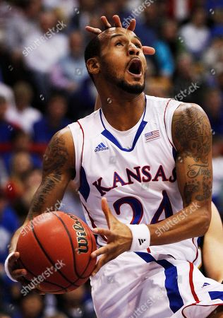 Stock Image of Travis Releford, Alex Giergen, Erique Gumbs. Kansas guard Travis Releford (24) drives past to the basket against Towson during the first half of an NCAA college basketball game, in Lawrence, Kan