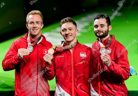 Nile Wilson of England with the gold medal, James Hall of England with the Silver medal and Cory Patterson of Canada with the silver medal after the Men's Horizontal Bar Final on Day Five of the Gold Coast Commonwealth Games 2018.
