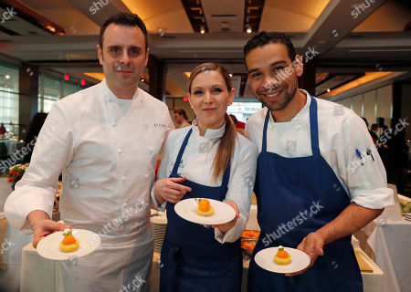 Chef Markus Glocker of Batard, left, poses for a photograph with members of his staff holding a dessert they created at a benefit for Careers through Culinary Arts Program, or C-CAP, in New York