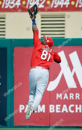 St. Louis Cardinals right fielder Anthony Garcia leaps into the air to catch a ball hit by Miami Marlins' Dan Black for an out during the sixth inning of an exhibition spring training baseball game, in Jupiter, Fla