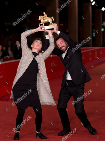 Director Alberto Fasulo, right, and his wife, producer Nadia Trevisan, hold the Golden Marc'Aurelio Award for Best movie 'Tir' as he poses for photographers at the 8th edition of the Rome International Film Festival, in Rome