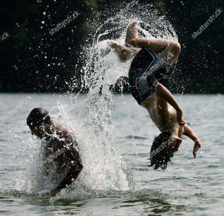 Freddie Roman, 13, right, of Waltham, Mass., is flipped into the water from the shoulders of Joey Marrero, 27, also of Waltham, as they keep cool at Walden Pond in Concord, Mass