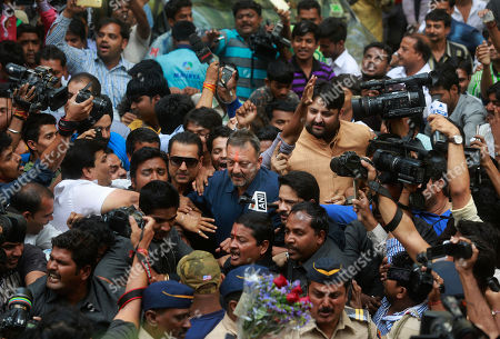Bollywood actor Sanjay Dutt, left, surrounded by his fans and media arrives at his residence in Mumbai, India, . Bollywood actor Sanjay Dutt walked free Thursday after completing his five-year prison sentence for illegal weapons possession in a case linked to the 1993 terror attack in India's financial capital Mumbai