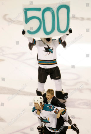 Jeremy Roenick, Brett Roenick. San Jose Sharks' center Jeremy Roenick skates with his son Brett on his back at the end of their NHL hockey game against the Phoenix Coyotes in San Jose, Calif., . In the background the team mascot, S.J. Sharkie, holds up a sign honoring Roenick's 500th career goal which came in the second period of the game. San Jose won the game, 4-1