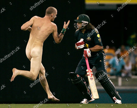 Australia's Andrew Symonds, foreground, prepares to check a pitch invader to the ground during the second final of their tri-nations one day international cricket series against India at Brisbane, Australia, . India made 258 in their innings