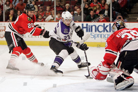 Dustin Brown, Robert Lang, Nikolai Khabibulin. Los Angeles Kings' Dustin Brown, center, takes a shot against Chicago Blackhawks goalie Nikolai Khabibulin, right, of Russia, as Robert Lang, of the Czech Republic, defends during the overtime period of an NHL hockey game, in Chicago. Brown scored a goal on the shot to give the Kings a 3-2 victory