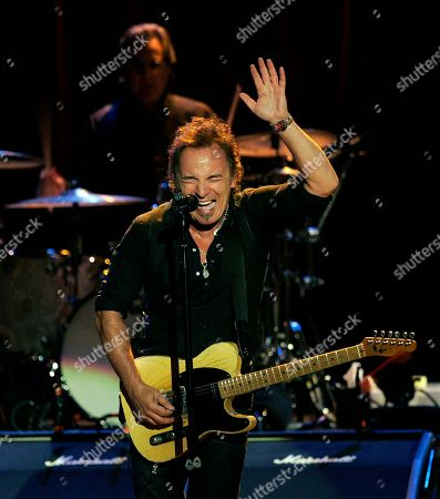 Bruce Springsteen waves as he sings at the Count Basie Theatre, in Red Bank, N.J., as he and the E Street Band play a benefit concert for the renovation of the Count Basie Theatre