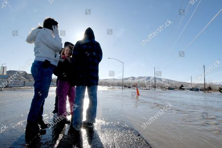 Tiffany Kilby and her three children Kierra, Korey and Brandon, look across the flooded intersection of Ricci Lane and Crimson Lane where Kilby's parents live and are cutoff from leaving their house, in Fernley, Nev