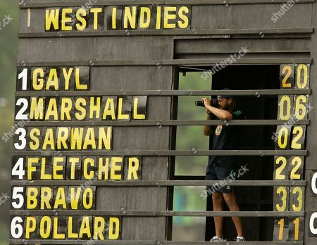 Australia's cricket player Andrew Symonds takes pictures from within the scoreboard that shows the runs scored by West Indies' batsmen on their first One Day International cricket match at the Arnos Vale cricket ground in Kingstown, St. Vincent, . Australia won by 84 runs