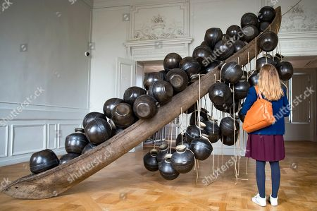 A visitor looks at a work entitled 'Jal Mein Kumbh, Kumbh Mein Jal Hai' by Indian artist Subodh Gupta as part of an exhibition of his work at the Monnaie de Paris, in Paris, France, 10 April 2018. The exhibition runs from 13 April to 26 August 2018.