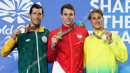 From left, Silver medalist Bradley Tandy from South Africa, Gold medalist Benjamin Proud from England and bronze medalist Cameron McEvoy during ceremonies in the men's 50m freestyle final at the Aquatic Centre during the 2018 Commonwealth Games on the Gold Coast, Australia