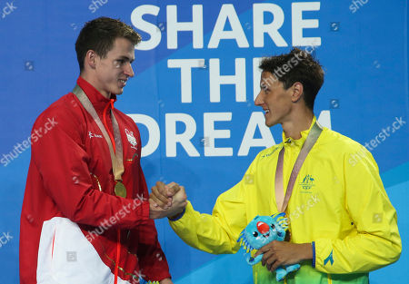Gold medalist Benjamin Proud, left, from England and bronze medalist Cameron McEvoy from Australia during ceremonies in the men's 50m freestyle final at the Aquatic Centre during the 2018 Commonwealth Games on the Gold Coast, Australia