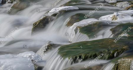 Ice-covered stones in the river bed of the Triesting, Pottenstein, Lower Austria, Austria