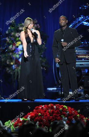 Mariah Carey gesturing towards the casket bearing the body of Michael Jackson as she sings with Trey Lorenz