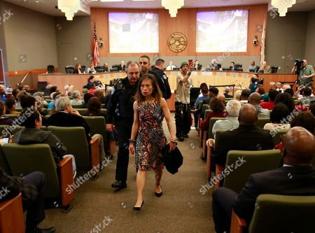 An attendee of a Sacramento City Council meeting where the shooting of Stephon Clark by Sacramento Police was discussed, is escorted from the council chamber after interrupting other speakers, in Sacramento, Calif. Sacramento Police Chief Daniel Hahn told City Council members that more video of last month's shooting of Clark, an unarmed black man, will be released within a week