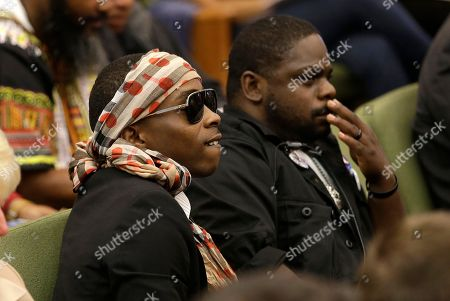 Stevante Clark, left, the brother of Stephon Clark, who was shot and killed by Sacramento police, listens as Sacramento Police Chief Daniel Hahn answers questions concerning the shooting of Clark, at a meeting of the Sacramento City Council, in Sacramento, Calif. Hahn told City Council members that the department is working to give new officers training and experience in avoiding implicit racial bias