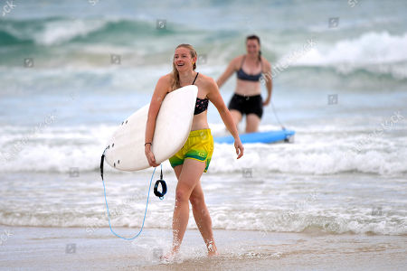 Australian Paralympic skier and track and field athlete Jessica Gallagher (L) and former Australian cyclist Anna Meares (R) leave the water after taking part in a surf lesson with Austrlaian surfer Mick Fanning (not pictured) during the XXI Commonwealth Games at Kirra Beach on the Gold Coast, Queensland, Australia, 11 April 2018.