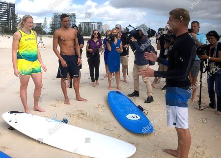 Chad Le Clos, Mick Fanning. Australian surf legend Mick Fanning, right, talks to South African swimmer Chad Le Clos, right, and Australian para cyclist Jessica Gallagher during a surf lesson at Kirra Beach on the Gold Coast, Australia, . Le Clos accepted the offer of a surfing lesson at Fanning's local Kirra Beach the morning after completing his swimming program at the Commonwealth Games, where he won five medals for South Africa, with one reservation. He wanted to know if there were any sharks in the water