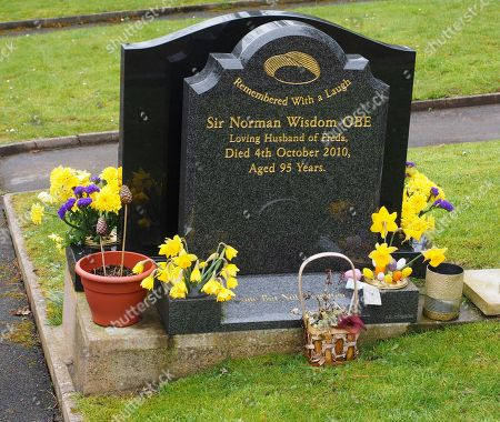 Grave of film actor and comedian Sir Norman Wisdom OBE at St Bridget church (Bride parish church) Isle of Man. He died 4th October 2010 at a nursing home Rushen, Isle of Man