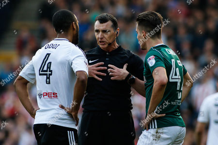 Referee, Neil Swarbrick talks to Denis Odoi of Fulham and Sergi Canos of Brentford following an altercation