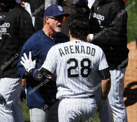 Nolan Arenado, Mark McGwire. San Diego Padres bench coach Mark McGwire, left, restrains Colorado Rockies' Nolan Arenado after he charged the mound following getting hit by a pitch from Padres starting pitcher Luis Perdomo in the third inning of a baseball game, in Denver