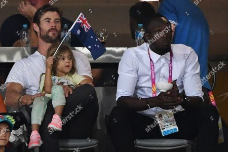 Stock Picture of Australian actor Chris Hemsworth (L) holding his daughter India Rose and retired Jamaican sprinter Usain Bolt watch the athletics competition at the XXI Commonwealth Games in Carrara Stadium on the Gold Coast, Australia, 12 April 2018.