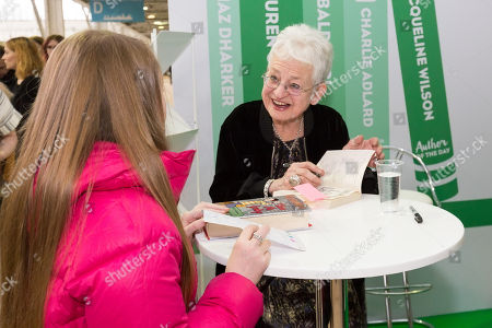 Dame Jacqueline Wilson signs one of her books brought by a young girl fan at The Book Fair 2018.