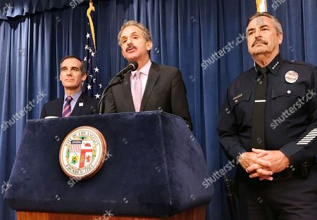 """Los Angeles City Attorney Mike Feuer, middle, is flanked by Police Chief Charlie Beck, right, and Mayor Eric Garcetti during a press conference in Los Angeles . A federal judge in Los Angeles has issued a nationwide injunction barring the Justice Department from awarding priority consideration for a community policing grant if they agreed to cooperate with immigration officials. Feuer said the ruling was a """"complete victory"""