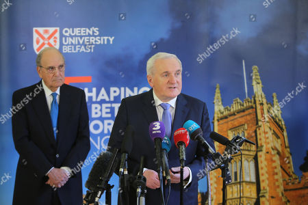 Former Taoiseach Mr Bertie Ahern speaks while Senator George Mitchell lsitens during a press conference at Queen's University Belfast