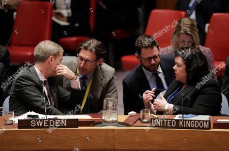 Olof Skoog, left, Sweden's ambassador to the UN, and Karen Price, right, United Kingdom ambassador to the United Nations, talk to members of their teams during a Security Council meeting, at United Nations headquarters