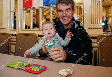 Elite runner Arne Gabius, of Germany, holds his 5 1/2-month-old son, Frederik, during a news conference, in Boston. The 122nd running of the Boston Marathon is scheduled for Monday