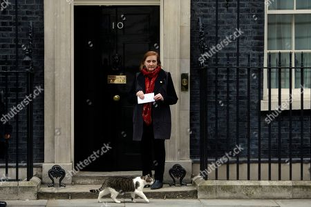 Lawmaker Emma Dent Coad prepares to hand in a letter of protest to 10 Downing Street, as Larry the official cat of 10 Downing Street walks past, part of a demonstration organised by the Stop the War Coalition against possible military intervention or bombing by western allies in Syria, in London, . Amid escalating global tensions over Syria, President Donald Trump and other world leaders weighed options for responding - possibly with military strikes - to the Syrian government's suspected chemical weapons attack against civilians