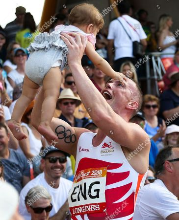 England's Richard Kilty lifts a baby girl after they won gold during the men's 4x100 relay at Carrara Stadium during the Commonwealth Games on the Gold Coast, Australia