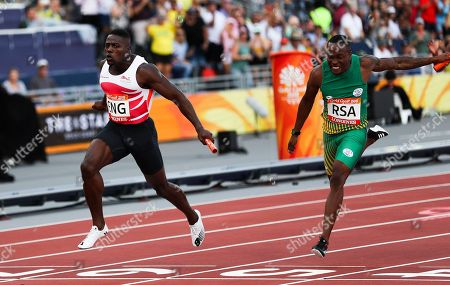 England's Harry Aikines-Aryeetey, left, crosses the line to win gold at the men's 4x100 relay at Carrara Stadium during the Commonwealth Games on the Gold Coast, Australia
