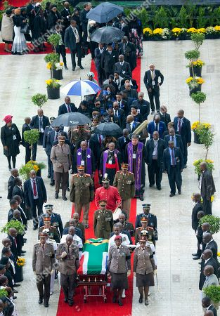 A military honor guard carries anti-apartheid activist Winnie Madikizela-Mandela's coffin, wrapped in the flag of South Africa, out of Orlando stadium following her funeral service, in Soweto, South Africa, . Tens of thousands of people sang, cheered and cried as the flag-draped casket of anti-apartheid activist Winnie Madikizela-Mandela was escorted from her official funeral on Saturday, after supporters defended her complex legacy with poetry and anger