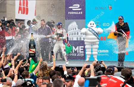 First placed DS Virgin Racing team driver Sam Bird, left, and third placed Techeetah team driver Andre Lotterer spray champagne during the podium ceremony of the Formula E Rome E-Prix auto competition in Rome