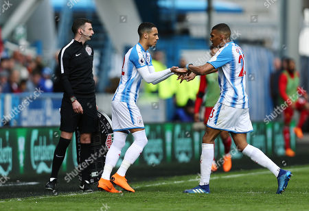 Collin Quaner of Huddersfield Town is replaced by Tom Ince as fourth official Michael Oliver looks on