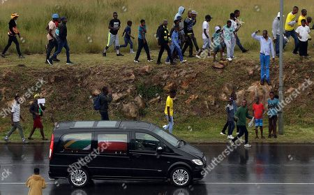 People follow the hearse carrying the coffin of anti-apartheid activist Winnie Madikizela-Mandela after her funeral service at the Orlando Stadium in Soweto, South Africa, on route for burial. Tens of thousands of people sang, cheered and cried as the flag-draped casket of anti-apartheid activist Winnie Madikizela-Mandela was escorted from her official funeral on Saturday, after supporters defended her complex legacy with poetry and anger