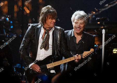 Jon Bon Jovi, Richie Sambora. Jon Bon Jovi, right, watches Richie Sambora play guitar during the Rock and Roll Hall of Fame Induction ceremony, in Cleveland