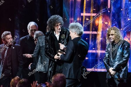 Howard Stern, Jon Bon Jovi, Tico Torres, Hugh McDonald. Tico Torres, left, Hugh McDonald, Howard Stern, and Jon Bon Jovi are seen at the 2018 Rock and Roll Hall of Fame Induction Ceremony at Cleveland Public Auditorium, in Cleveland, Ohio
