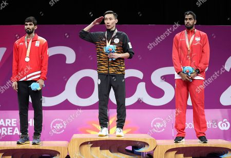 Gold medalist Lee Chong Wei of Malaysia, center, salutes, as silver medalist India's Srikanth Kidambi of India, left, and bronze medalist Rajiv Ouseph of England look on while Malaysian national anthem is played during the medal ceremony for men's singles badminton at Carrara Sports Hall during the Commonwealth Games on the Gold Coast, Australia