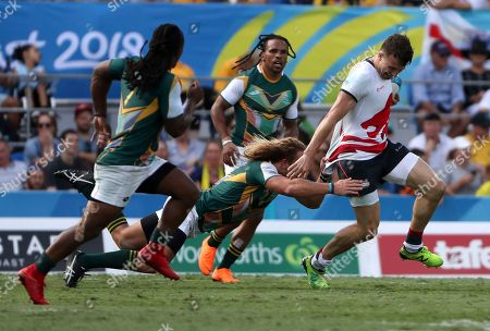 Stock Image of England's Alexander Davis runs away from South African defenders during their rugby sevens bronze medal match at Robina Stadium during the 2018 Commonwealth Games on the Gold Coast, Australia