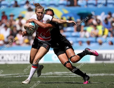England's Emily Scott, left, attempts to break the tackle of a New Zealand defender during their rugby sevens semifinal at Robina Stadium during the 2018 Commonwealth Games on the Gold Coast, Australia