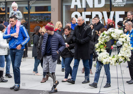 Boston Marathon Bombing victim Jeff Bauman (2L), who lost both of his legs from the explosion, walks past a wreath at Marathon Sports at 671 Boylston St., the location of the first explosion, during a memorial ceremony on the fifth anniversary of the Boston Marathon Bombing, n Boston, Massachusetts, USA 15 April 2018. On 15 April 2013, two homemade bombs detonated 12 seconds and 210 yards (190 m) apart at 2:49 p.m., near the finish line of the annual Boston Marathon, killing three people and injuring several hundred others. Brothers Dzhokhar Tsarnaev and Tamerlan Tsarnaev were eventually sought for the crime which Tamerlan bing killed during a  police shootout and Dzhokhar later captured, tried in court and sentenced to death and is currently awaiting appeal while in prison.