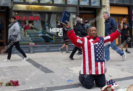 Christopher Nzenwa prays at a memorial outside of Marathon Sports at 671 Boylston St., the location of the first explosion, during a memorial ceremony on the fifth anniversary of the Boston Marathon Bombing, n Boston, Massachusetts, USA 15 April 2018. On 15 April 2013, two homemade bombs detonated 12 seconds and 210 yards (190 m) apart at 2:49 p.m., near the finish line of the annual Boston Marathon, killing three people and injuring several hundred others. Brothers Dzhokhar Tsarnaev and Tamerlan Tsarnaev were eventually sought for the crime which Tamerlan bing killed during a  police shootout and Dzhokhar later captured, tried in court and sentenced to death and is currently awaiting appeal while in prison.