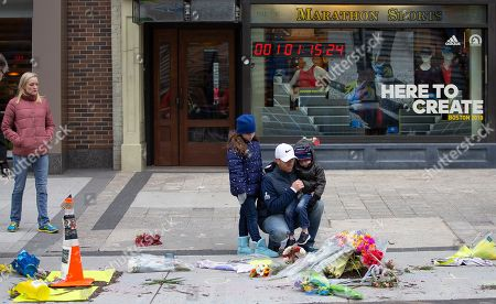 Stock Photo of People pause at a memorial on the ground outside of at Marathon Sports at 671 Boylston St., the location of the first explosion, following a memorial ceremony on the fifth anniversary of the Boston Marathon Bombing, n Boston, Massachusetts, USA 15 April 2018. On 15 April 2013, two homemade bombs detonated 12 seconds and 210 yards (190 m) apart at 2:49 p.m., near the finish line of the annual Boston Marathon, killing three people and injuring several hundred others. Brothers Dzhokhar Tsarnaev and Tamerlan Tsarnaev were eventually sought for the crime which Tamerlan bing killed during a  police shootout and Dzhokhar later captured, tried in court and sentenced to death and is currently awaiting appeal while in prison.