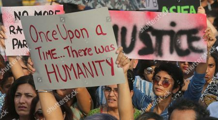 Indian film producer Kiran Rao, right, holds a placard during a protest against recent incidents of rape in the country, in Mumbai, India, . Violent crimes against women have been on the rise in India despite tough laws enacted in 2013