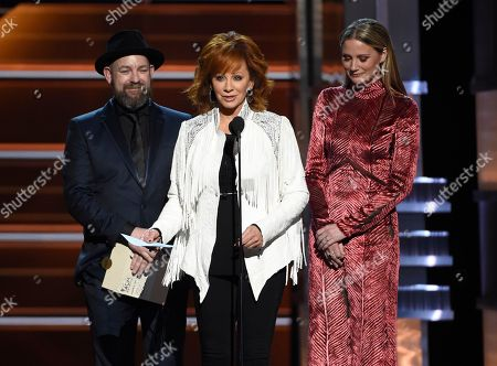 """Reba McEntire, Kristian Bush, Jennifer Nettles. Reba McEntire, center, accepts the award for album of the year for """"From A Room: Volume 1"""" on behalf of Chris Stapleton at the 53rd annual Academy of Country Music Awards at the MGM Grand Garden Arena, in Las Vegas. Looking on are presenters Kristian Bush, left, and Jennifer Nettles, right, of Sugarland"""