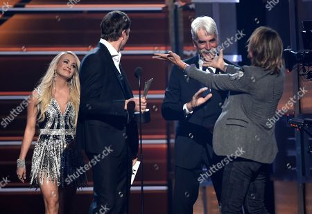 """Keith Urban, Carrie Underwood, Ashton Kutcher, Sam Elliott. Keith Urban, right, gestures to Carrie Underwood, left, fellow winner for the award for vocal event of the year for """"The Fighter"""" as presenters Ashton Kutcher, second left, and Sam Elliott, second right, look on at the 53rd annual Academy of Country Music Awards at the MGM Grand Garden Arena, in Las Vegas"""