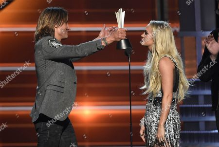 """Keith Urban, Carrie Underwood. Keith Urban, left, and Carrie Underwood accept the award for vocal event of the year for """"The Fighter"""" at the 53rd annual Academy of Country Music Awards at the MGM Grand Garden Arena, in Las Vegas"""